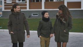 Familia feliz en la caminata Padre, madre y niño Caminan, pasan tiempo con su Mujer hermosa en una capa y una bufanda almacen de video