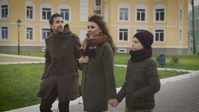 Familia feliz en la caminata Padre, madre y niño Están dando un paseo Mujer hermosa en la capa y la bufanda, sosteniéndose almacen de metraje de vídeo