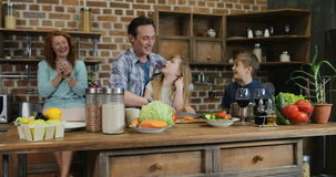 Familia feliz en la cocina que prepara la comida, madre que mira el padre y a los niños que cocinan junto en casa almacen de metraje de vídeo