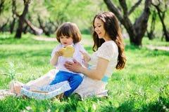 Familia feliz en la comida campestre para el día de madres Hijo de la mamá y del niño que come los dulces al aire libre en primav imagen de archivo libre de regalías