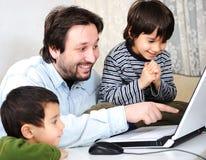 Familia feliz en la computadora portátil Foto de archivo libre de regalías