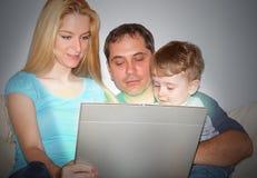Familia feliz en la computadora portátil de Compyter Imagenes de archivo