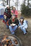 Familia feliz en la hoguera en invierno foto de archivo libre de regalías
