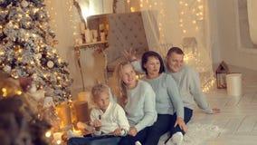 Familia feliz en la madre, el padre, el hijo y la hija de Christmass con primero plano del árbol de los christmass almacen de metraje de vídeo