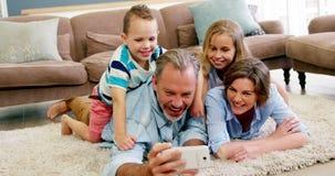 Familia feliz en la mentira en la manta y hablar un selfie en el teléfono móvil