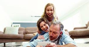 Familia feliz en la mentira en la manta y hablar un selfie en el teléfono móvil metrajes