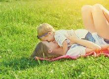 Familia feliz en la naturaleza la hija de la mamá y del bebé está jugando en Imagen de archivo