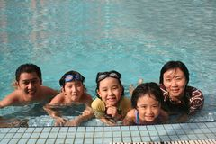 Familia feliz en la piscina Fotografía de archivo libre de regalías