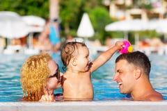 Familia feliz en la piscina Foto de archivo libre de regalías