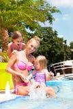 Familia feliz en la piscina, divirtiéndose, concepto de las vacaciones Foto de archivo libre de regalías