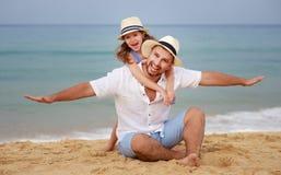 Familia feliz en la playa abrazo de la hija del padre y del niño en el mar imagenes de archivo