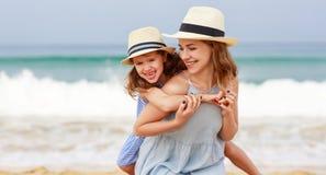 Familia feliz en la playa abrazo de la hija de la madre y del ni?o en el mar foto de archivo libre de regalías