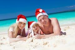 Familia feliz en la playa en los sombreros de Papá Noel, la Navidad de la celebración Imagen de archivo libre de regalías