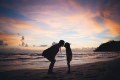 Familia feliz en la puesta del sol foto de archivo