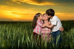 Familia feliz en la puesta del sol niño que besa a la mamá Fotos de archivo libres de regalías