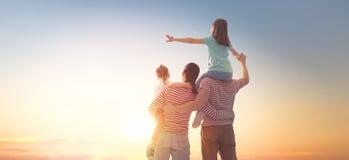 Familia feliz en la puesta del sol fotos de archivo