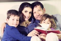 Familia feliz en la sonrisa de relajación de la cama mirando la cámara Fotos de archivo