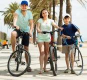 Familia feliz en las bicicletas del montar a caballo de las vacaciones Imagen de archivo