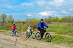 Familia feliz en las bicis, padre que completa un ciclo con los niños al aire libre Imágenes de archivo libres de regalías