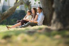 Familia feliz en los jardines de la ciudad que se relajan Foto de archivo libre de regalías
