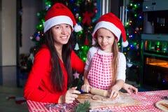 Familia feliz en los sombreros de Papá Noel que cuecen la Navidad Imagenes de archivo