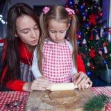 Familia feliz en los sombreros de Papá Noel que cuecen la Navidad Imágenes de archivo libres de regalías