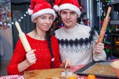 Familia feliz en los sombreros de Papá Noel que cuecen la Navidad Imagen de archivo libre de regalías