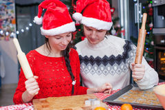 Familia feliz en los sombreros de Papá Noel que cuecen la Navidad Fotografía de archivo libre de regalías