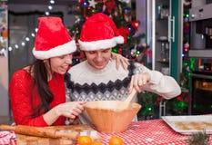 Familia feliz en los sombreros de Papá Noel que cuecen la Navidad Imagen de archivo
