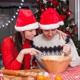 Familia feliz en los sombreros de Papá Noel que cuecen la Navidad Fotografía de archivo
