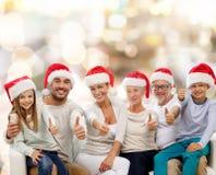 Familia feliz en los sombreros de santa que muestran los pulgares para arriba Imagen de archivo