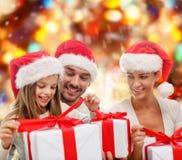 Familia feliz en los sombreros de santa que se sientan con las cajas de regalo Fotos de archivo