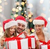 Familia feliz en los sombreros de santa que se sientan con las cajas de regalo Imagen de archivo