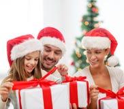 Familia feliz en los sombreros de santa que se sientan con las cajas de regalo Imágenes de archivo libres de regalías