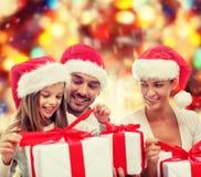 Familia feliz en los sombreros de santa que se sientan con las cajas de regalo Fotos de archivo libres de regalías