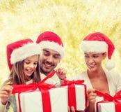 Familia feliz en los sombreros de santa que se sientan con las cajas de regalo Fotografía de archivo libre de regalías