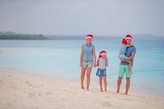 Familia feliz en los sombreros rojos de Papá Noel en la playa tropical que celebra la Navidad Foto de archivo libre de regalías