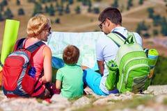 Familia feliz en montañas que discute la ruta Foto de archivo libre de regalías