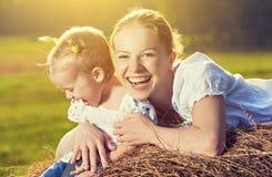 Familia feliz en naturaleza del verano Hija en el heno, paja de la madre y del bebé Fotografía de archivo