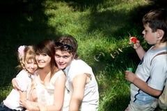 Familia feliz en parque con las burbujas. Imagen de archivo libre de regalías