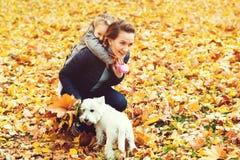 Familia feliz en paseo del otoño Madre, hija y su perro jugando en el parque del otoño Familia que disfruta de la naturaleza herm fotografía de archivo libre de regalías