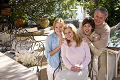 Familia feliz en patio asoleado Imágenes de archivo libres de regalías