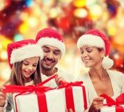 Familia feliz en sombreros del ayudante de santa con las cajas de regalo Imágenes de archivo libres de regalías