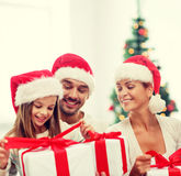 Familia feliz en sombreros del ayudante de santa con las cajas de regalo Foto de archivo