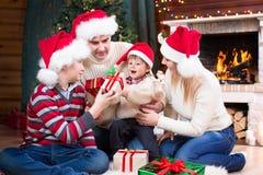 Familia feliz en sombreros rojos con los regalos que se sientan en Foto de archivo libre de regalías