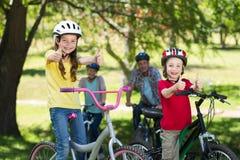 Familia feliz en su bici en el parque con los pulgares para arriba Fotografía de archivo libre de regalías