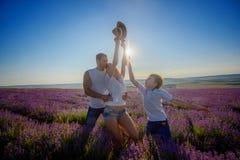 Familia feliz en un campo de la lavanda en puesta del sol imagenes de archivo