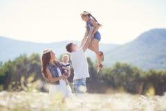 Familia feliz en un campo de margaritas florecientes imagenes de archivo