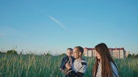 Familia feliz en un campo de trigo entre las espiguillas verdes El padre mantiene a la hija sus brazos Junto alegre aumente su almacen de video