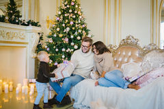 Familia feliz en un cuarto hermoso con una chimenea Imagenes de archivo